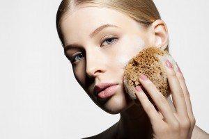 woman exfoliates face with a sponge